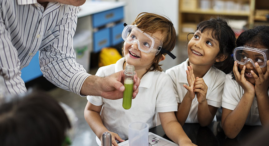 4 kids looking at teacher while he holds a test tube with a green substance inside